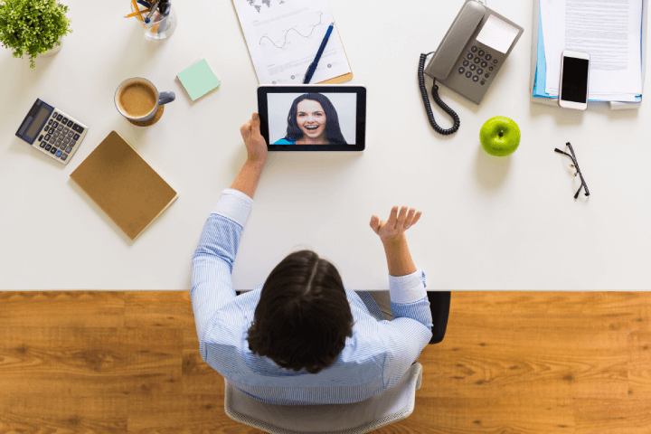 woman holding video call with coworker using tablet
