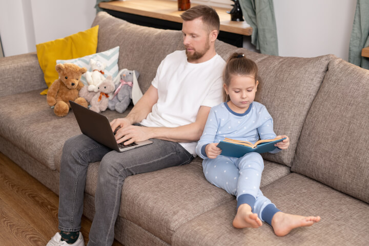 man on laptop with his daughter reading on sofa