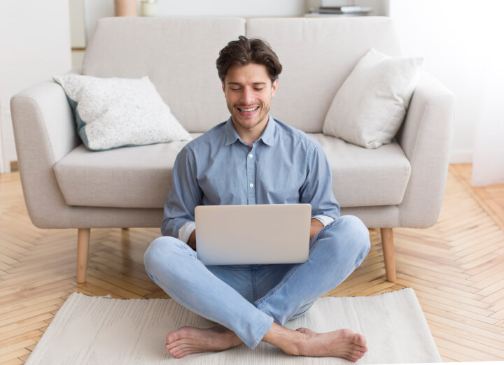 smiling man sitting on floor using laptop