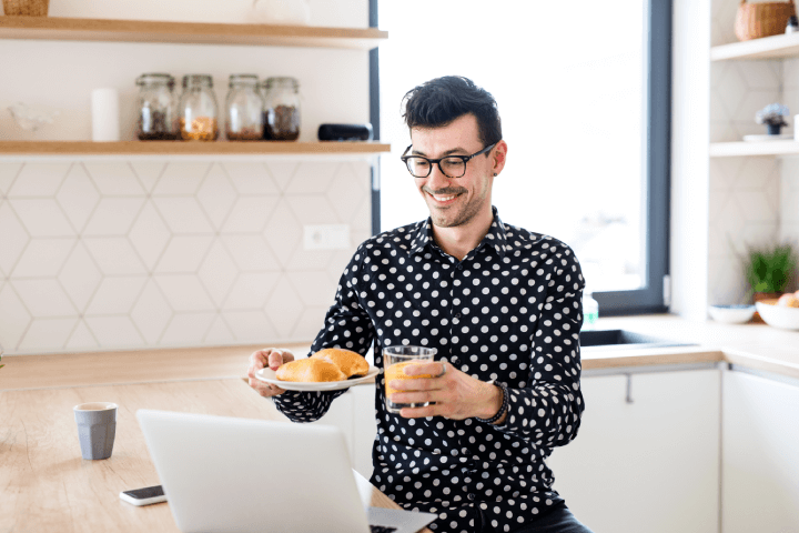 man working from home showing coworkers his breakfast