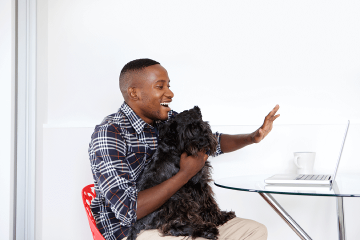 man on video call shows coworkers his dog