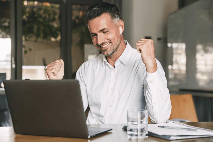 man celebrating in front of laptop