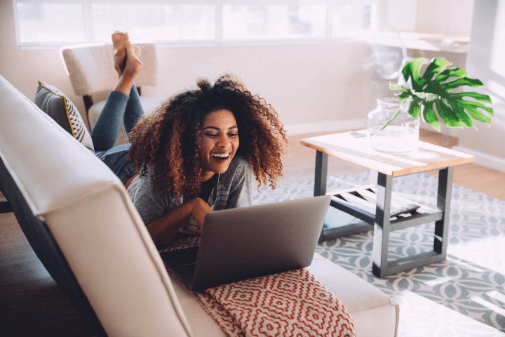 woman laughing while using messaging app on her laptop
