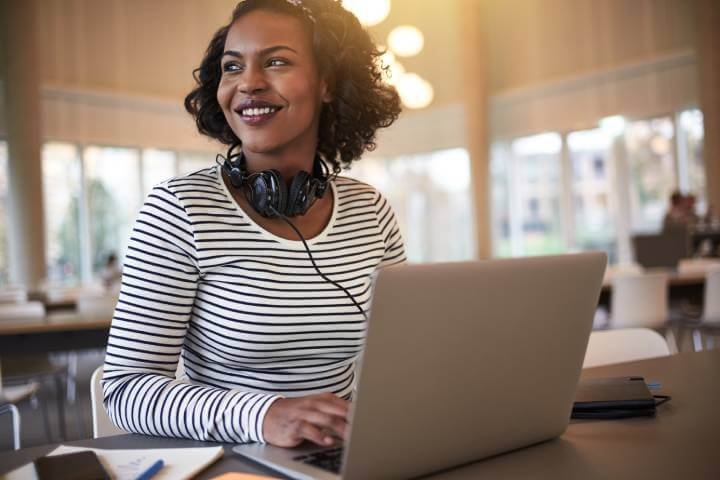 woman smiling while using laptop for social learning