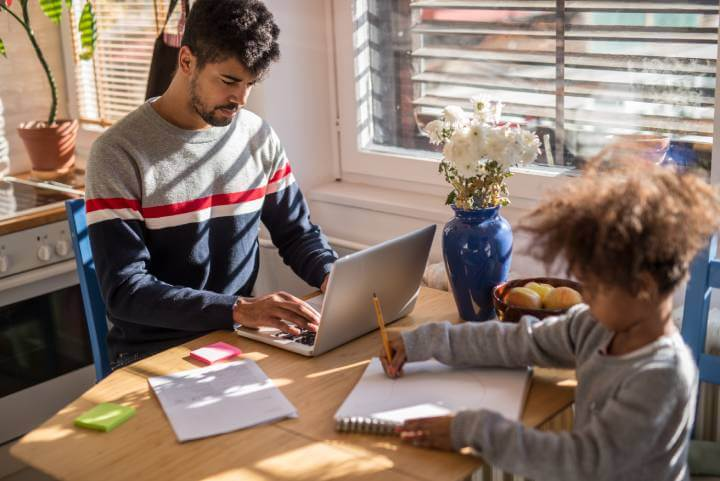 man works from home with his son