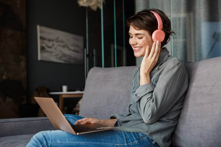 woman using laptop with headphone to learn online