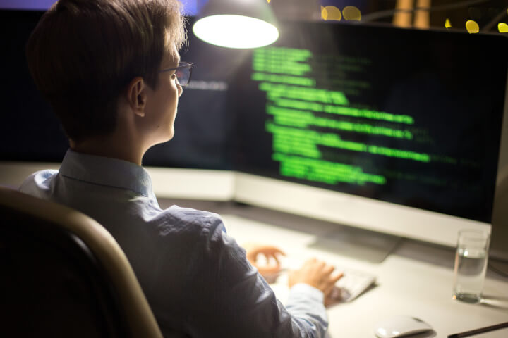 man coding as part of his cyber security skills